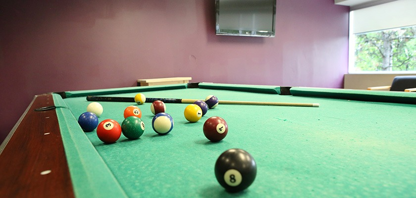 Close-up of a pool table. There is a TV mounted to the wall in the background.
