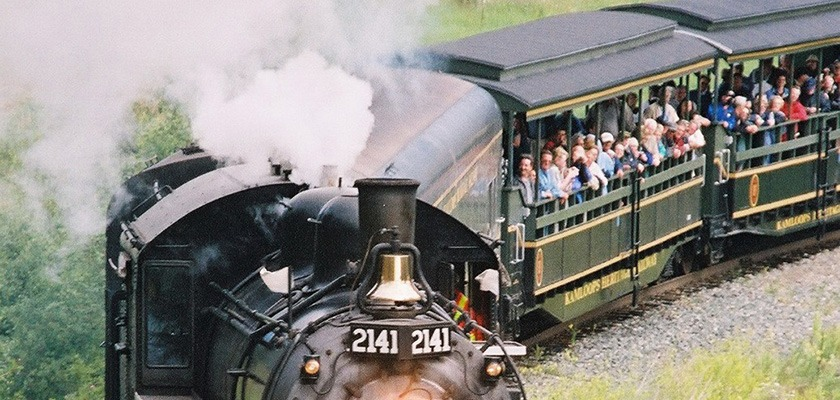 Image of a steam-train. There are open air passenger cars with people looking outside.