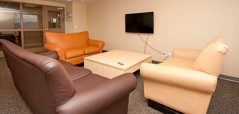 Image of a lounge at RCC Kamloops - there are couches and a TV mounted to the wall.