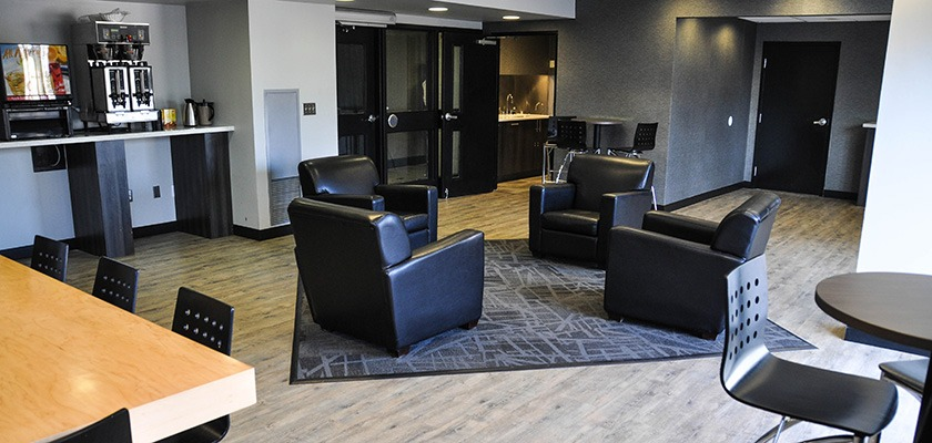 Lounge at RCC - Kitchener-Waterloo - there is a seating area, and a rug in the centre of the image.