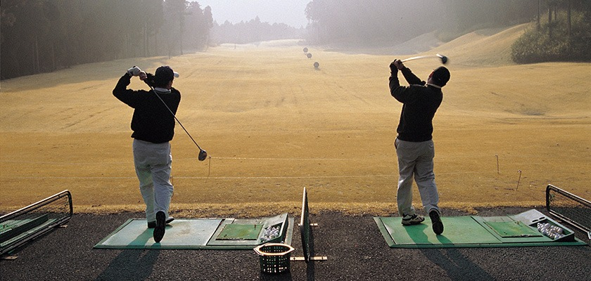 Image of two golfers at a driving range on a foggy morning. Both are mid-swing.