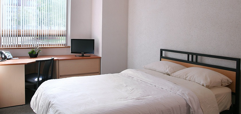 Image of a bedroom. There is a double bed, a desk and chair as well as a dresser with a TV on it.