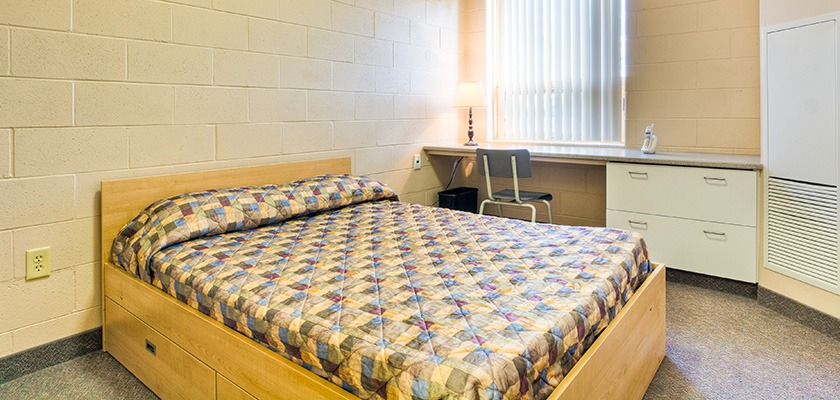 Bedroom at RCC - Sudbury North. There's a double bed, and a desk and a chair in the background.