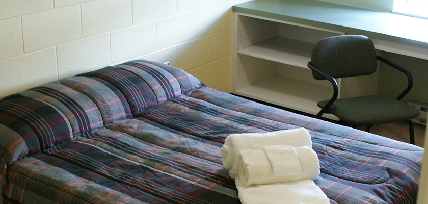 Image of a bed, there's a duvet with white towels rolled up on it. In the background is a desk and a chair.
