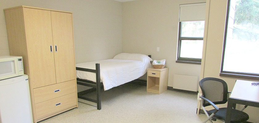 Image of a room at Sibley Hall. There's a small fridge, microwave, and a single bed.