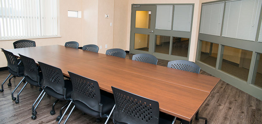Meeting space at RCC - Windsor. There's a boardroom table set-up, with chairs around it.