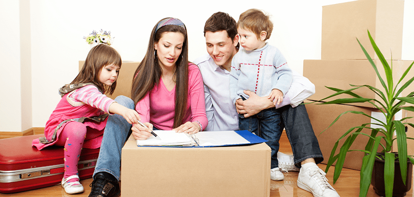 Image of a family of four surrounded by packing boxes looking at a list the mother is writing.