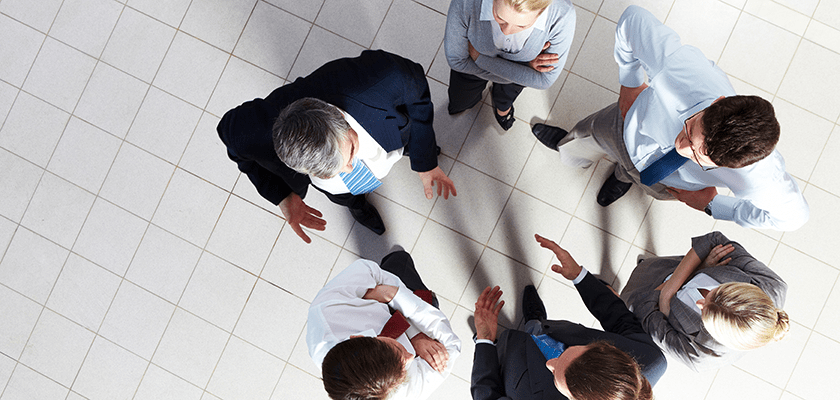 Aerial view of people in business attire standing in a circle talking.