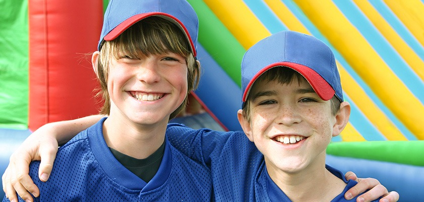 Two smiling children wearing blue and red baseball hats.