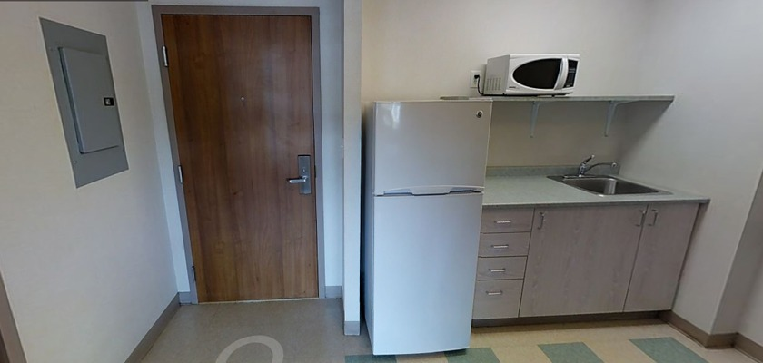 Kitchenette at RCC - Ottawa West, there is a fridge, a microwave and a counter with a sink.