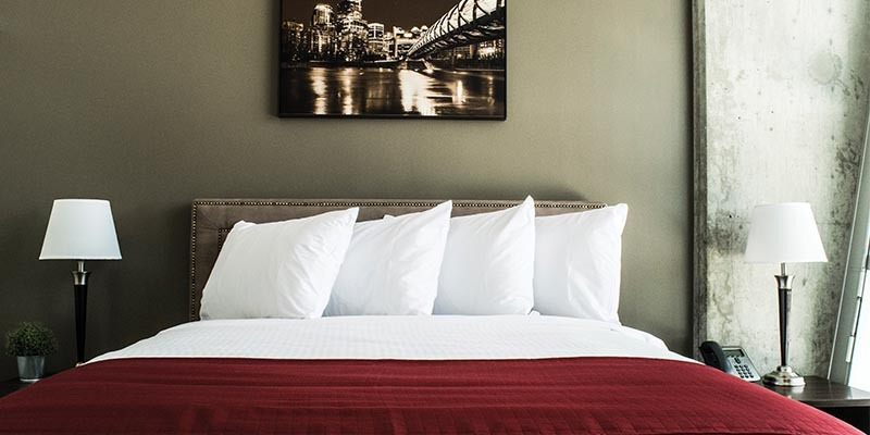Image of a bed in the corporate suites at RCC - Calgary. There are four pillows, a lamp on both sides of the bed, and a black and white photo of Calgary above the bed.