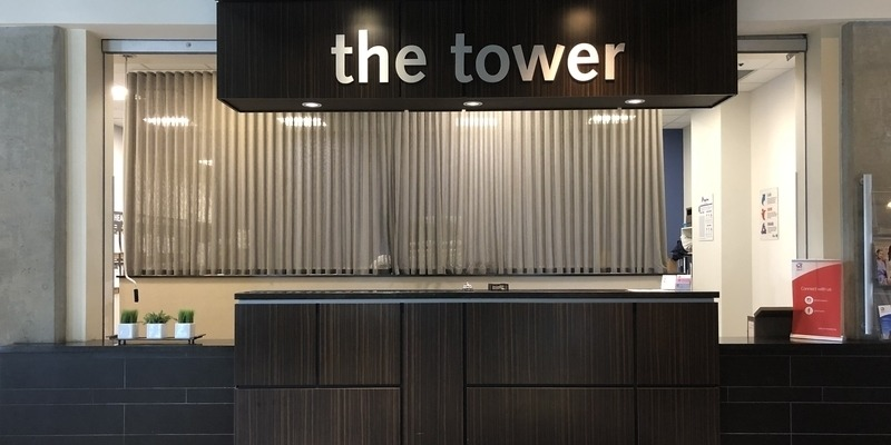 Front Desk at RCC - Calgary - there's a large sign that says 'the tower' above the front desk.