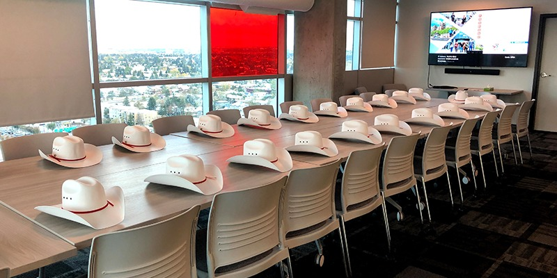 The boardroom at RCC-Calgary - there are cowboy hats in front of every seat, and a large TV on teh wall.
