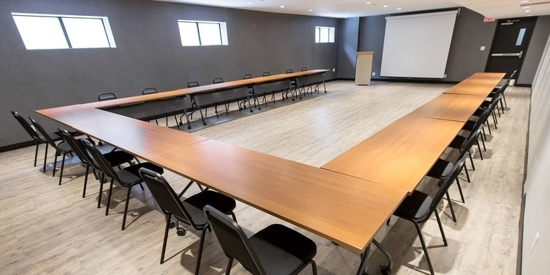 Meeting space at RCC - Kitchener-Waterloo. There are rows of tables and chairs facing a projector screen.