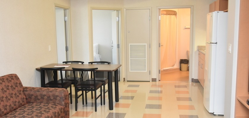 The Kitchenette at RCC-London. There is a table and four chairs, a couch, and a fridge.