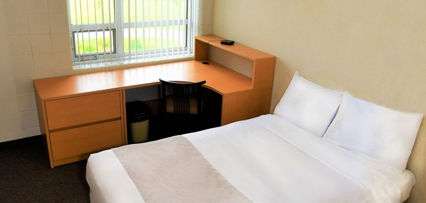 Image of a bedroom at RCC - London, there is a double bed, a two-drawer dresser, and a desk with chair.