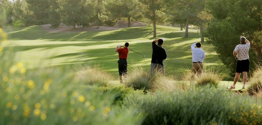 Photo of four golfers - one person has just swung, the three others are watching the ball.