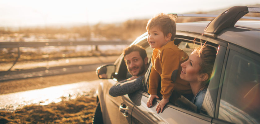 Image of a family on a roadtrip, leaning out the car window.