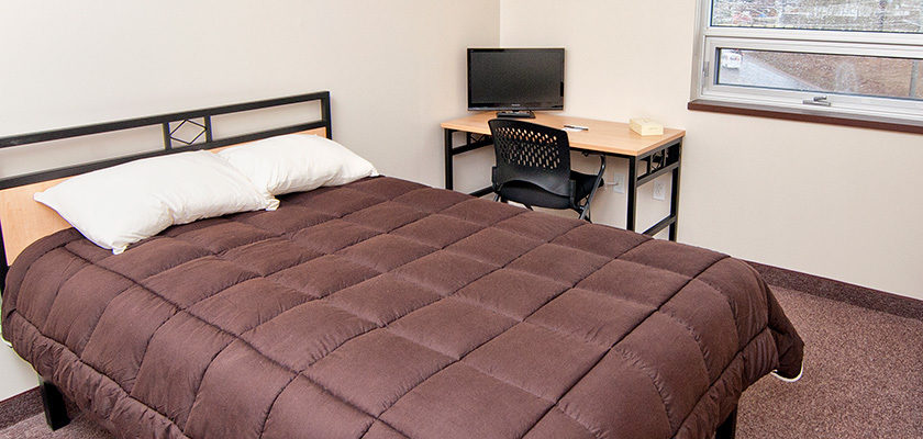 Image of a bedroom at RCC - North Bay. There is a double bed, and a desk, chair and TV.