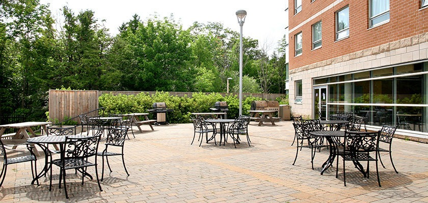 Image of Patio with BBQ - at RCC - Oshawa. There is a table, chairs on a large paved area.