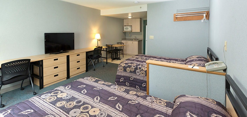 Image of a bedroom at Oshawa - there is a double bed, a desk with a chair, and a dresser.